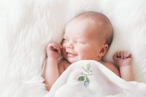 sleeping newborn under a blanket - Sleepyhead Consulting